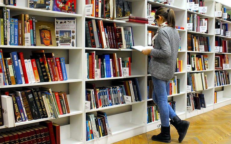 Kind met opengeslagen boek n de hand, staande voor grote boekenkast