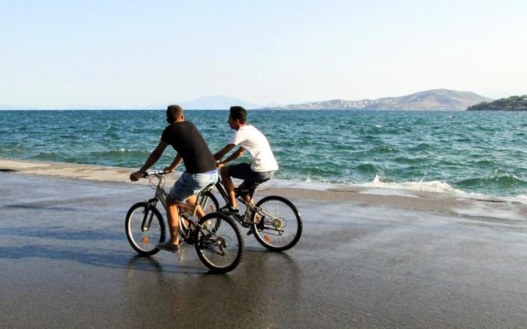 Twee mannen fietsen langs de zee op de boulevard