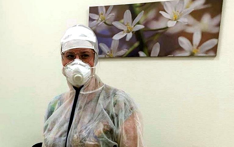 Vrouw met mondkap en beschermingskleding tegen besmetting coronavirus
